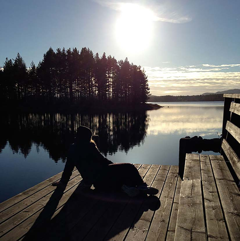 En person kopplar av på en brygga. Solen lyser