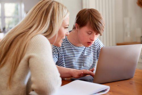 Två fokuserade personer jobbar tillsammans med hjälp av en dator vid ett bord