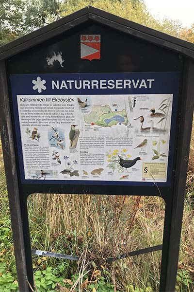 Bild på en skylt där det står om naturreservat under promenad runt Ekebysjön