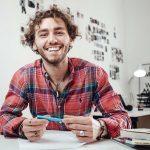 Glad person ler mot kameran och håller i en penna
