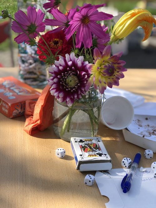 Spelar sällskapsspel vid ett bord med blommor på.