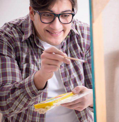 En glad person står och målar