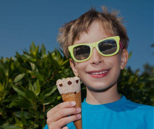 Glad person äter glass en solig dag