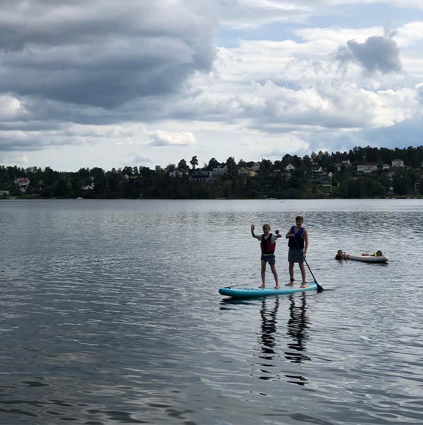 Två glada personer åker supboard vid Edsviken