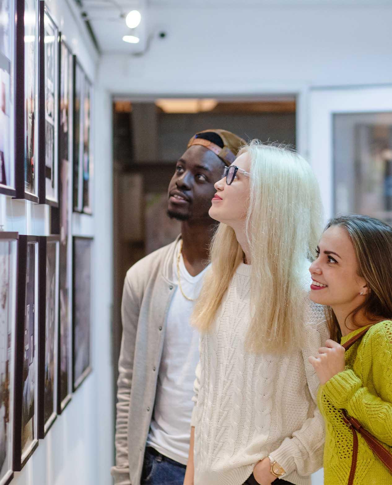 Tre personer står glada och intresserade och kollar på konst
