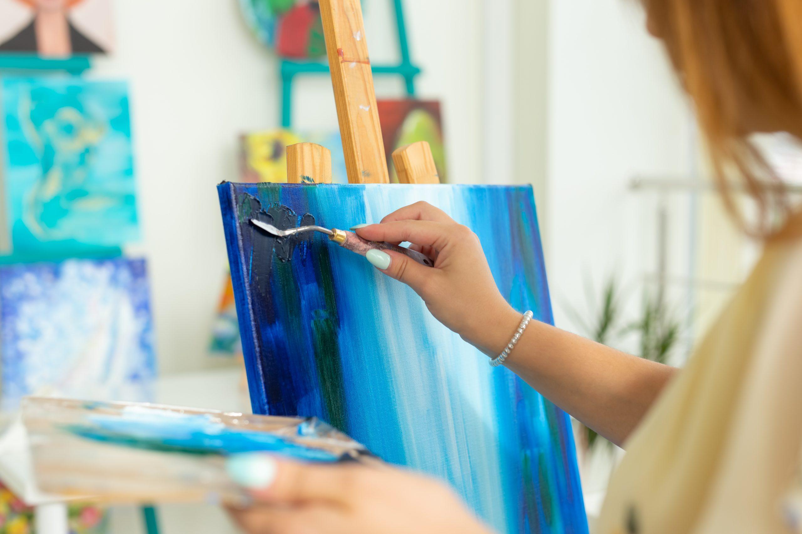 Person målar med olika nyanser blått