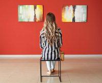 Person står och betraktar konst på väggen