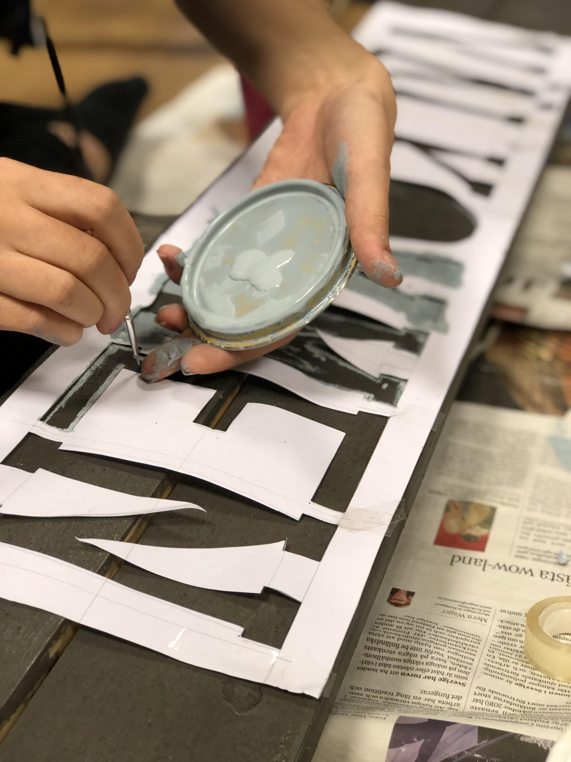 Person håller på att måla bokstäver på en skylt